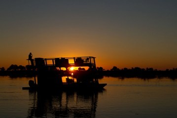 A spectacular sunset over the Linyanti river during a barge cruise at Kings Pool camp